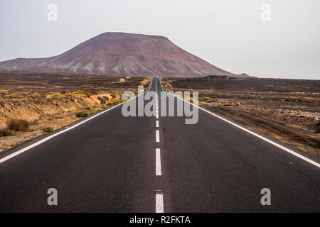long way straight road in the middle of a nobody there landscape in fuerteventura to cross the island and move. alternative wind lifestyle living in palce where nobody else stay. spirit of adventure enjoying traveling - Stock Photo