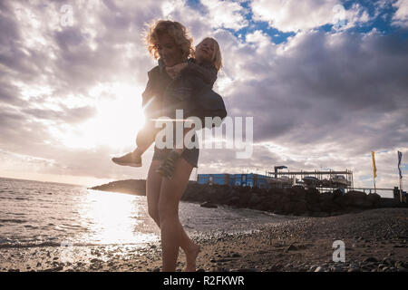 young woman mother carry on the back like a backpack and travel concept his young boy son over the beach enjoying the outdoor vacational activity together in friendship - female and male playful - Stock Photo