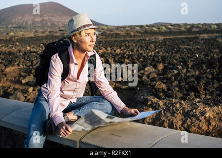 young beautiful lonely traveler woman looking at the map to choose her next destination and adventure. backpackers life and wanderlust feeling concept. cheerful nice blonde in alternative vacation lifestyle - Stock Photo