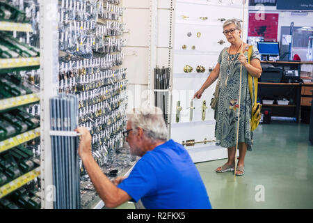 Senior adult couple in hardware shop together looking for and choosing stuffs to build or repair furnitures or other things at home. mature people  working and doing shoping together - Stock Photo