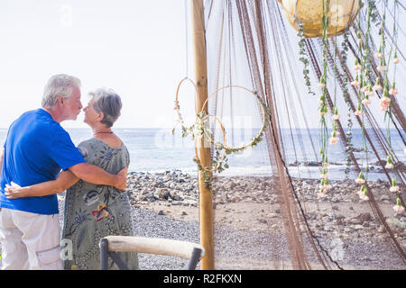 happy senior adult couple white hair stay together hugging and kissing with love after an entire life married. vacation and lifestyle outdoor concept for nice caucasian people in love aged