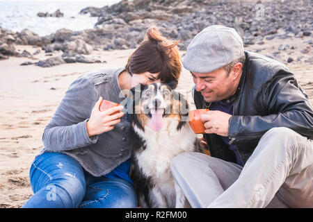 family with a border collie dog doing pic nic activity on the beach in vacation, summer lifestyle with friends concept. old style and vintage filter. tea break time - Stock Photo