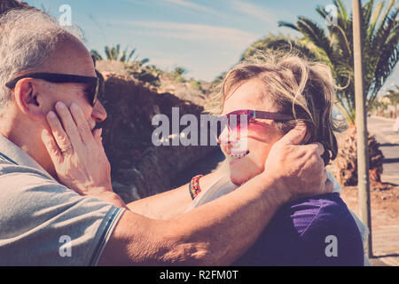 Elderly couple with white hair pampers and hugs each other in the open air under the sun in Tenerife - Stock Photo