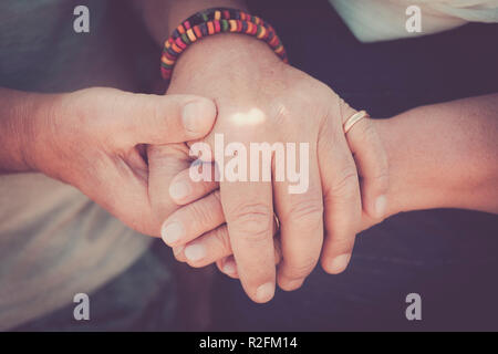 always tegether concept for a pair of elderly senior hands touching and staying together. Love moment for a life together - Stock Photo