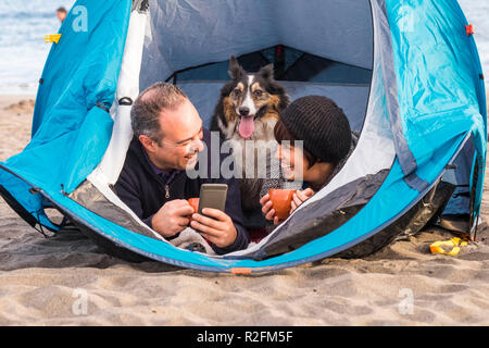 nice beautiful paople with cute puppy inside a tent using cellular phone to send message or take picture. beach camping freedom alternative vacation in tenerife with your best friends dog - Stock Photo