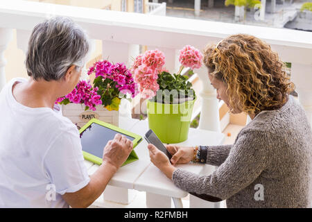 two adults woman different ages like mother and doughter use mobile technology tablet and smartphone outdoor in the terrace. happy search on internet for modern lifestyle - Stock Photo