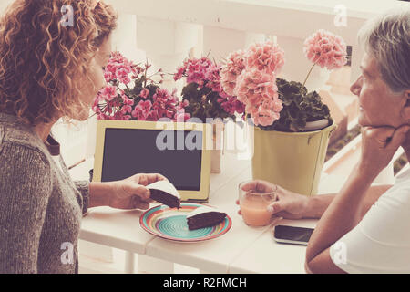 outdoor leisure activity talling storie for two caucasian women outdoor on the terrace, cake, fruit juice and tablet with internet and mobile phone for a nice afternoon - Stock Photo