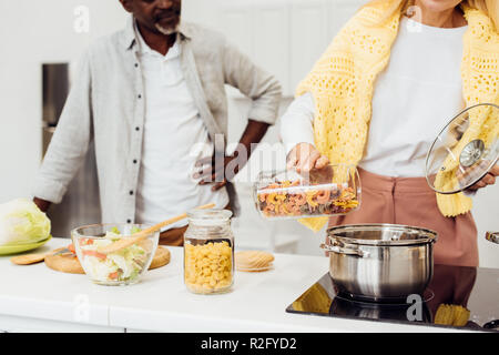 cropped view of woman standing near african american man and cooking pasta - Stock Photo