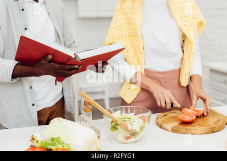 cropped view of interracial couple cooking dinner together at kitchen - Stock Photo