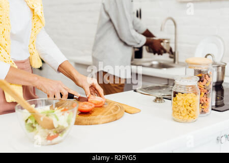 cropped view of couple cooking dinner together at home - Stock Photo