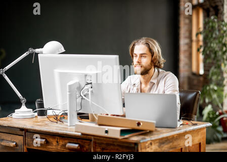 Handsome man working with laptop and computer sitting at the table in the modern home or office interior