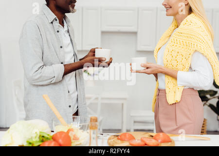cropped view of mature blonde woman and african american man drinking coffee together at kitchen - Stock Photo