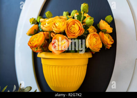 Artificial orange rose flowers in vase on wall - Stock Photo