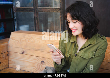 Happy young beautiful woman with green jacket using her smart phone sitting in a cool cafe while having a coffee. - Stock Photo