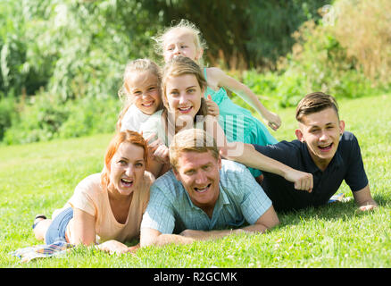cheerful large family with four different age children resting on the green meadow in park on summer day - Stock Photo