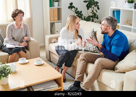 Angry wife showing sms from mistress to husband at psychology se - Stock Photo