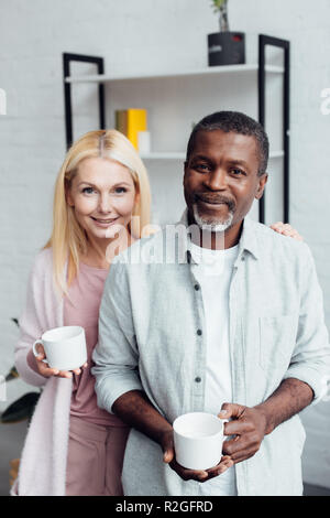 happy mature woman with african american holding white cups - Stock Photo