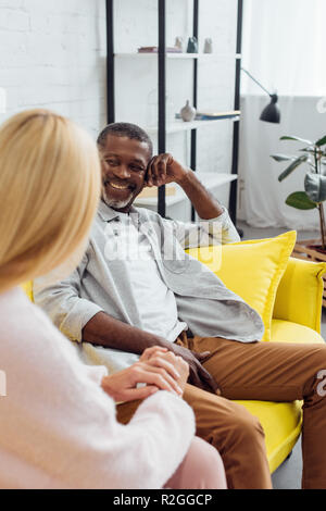 smiling mature african american man sitting on sofa and speaking with blonde woman - Stock Photo