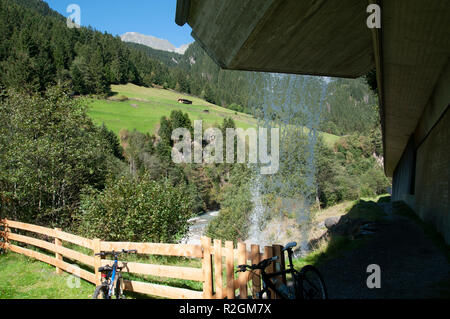 Tyrolean Alpine landscape as seen through a curtain of water from behind a waterfall. Photographed in Stubai Valley, Tyrol, Austria - Stock Photo