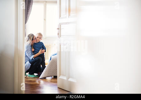 Young mother kissing her toddler son inside in a bedroom. Copy space. - Stock Photo