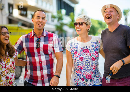 Cheerful two couples walking in front of apartments - Stock Photo