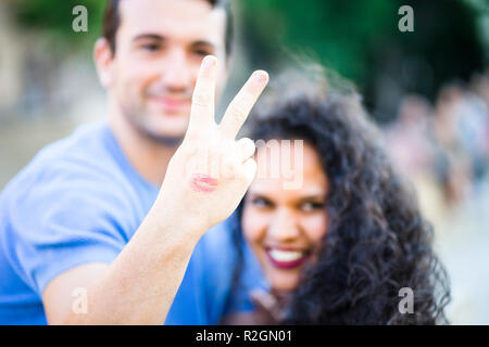 Happy young couple showing peace sign with visible lipstick print on his hand - Stock Photo