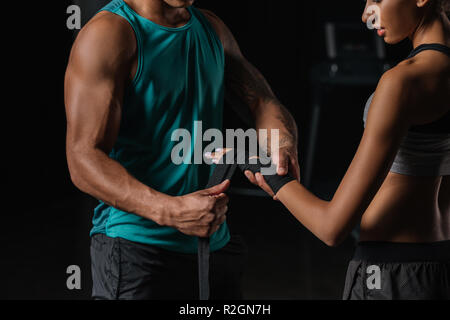 cropped image of male trainer with tattooed hand wrapping female boxer hand in boxing bandage at gym - Stock Photo