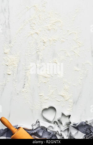 Baking background for baking Christmas cookies with cutters and rolling pin on white marble table with flour. Top view, copy space for text. - Stock Photo