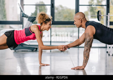 side view of couple of athletes shaking hands while doing plank at gym - Stock Photo