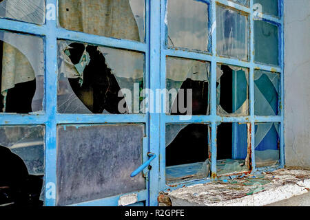 Deserted and dilapidated store front with broken window panes. Economic hardship and depression. Photographed in Athens, Greece - Stock Photo