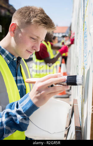 Group Of Helpful Teenagers Creating And Maintaining Community Art Project - Stock Photo