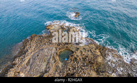Aerial drone view of the ocean and waves crashing on rocks.Man alone wearing blue jacket enjoying the nature. - Stock Photo