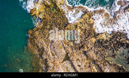 Aerial drone view of the ocean and waves crashing on rocks.A man alone swimming on a natural pool. - Stock Photo