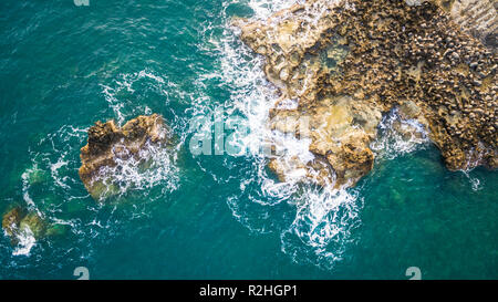 Aerial drone view of the ocean and waves crashing on rocks. - Stock Photo