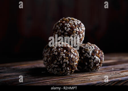 Healthy energy organic vegetarian bites with nuts, dates, honey and sesame on a dark wooden background.