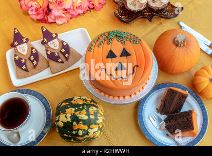 Novelty cake decorated with marzipan and icing in Halloween pumpkin theme. - Stock Photo