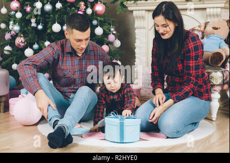 young parents family man and woman with child opening christmas gift box - Stock Photo