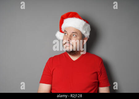 mid adult man wearing santa hat and red t-shirt looking up to copy space - real people christmas concept - Stock Photo