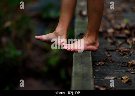 Close-up of a boy's dirty feet standing on a footbridge in the forest, United States - Stock Photo