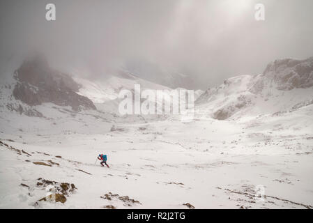 Man hiking up a snow covered mountain, Huesca, Pyrenees, Spain - Stock Photo
