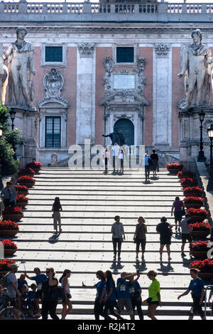 Tourists on the steps leading up to the Piazza del Campidoglio and the Capitoline Museums, atop the Capitoline Hill, looking towards the facade of the - Stock Photo
