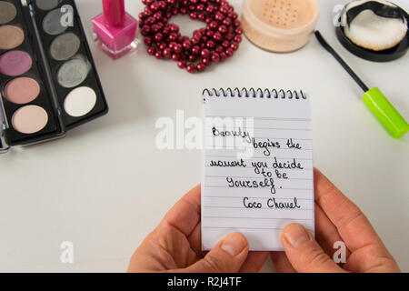 Woman hand holds Coco Chanel quotes written on a block note, pearl accessories and make up on white background, inspiration phrase 'Beauty begins the  - Stock Photo