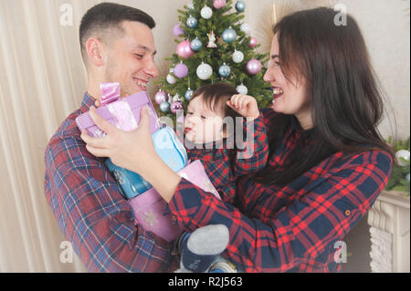 happy family mother father baby with gift boxes near christmas tree with toys - Stock Photo