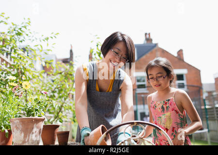 Mother and daughter gardening in sunny yard - Stock Photo