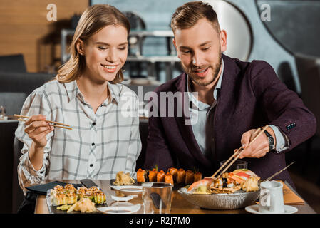 Attractive lovely couple eating together sushi rolls in restaurant - Stock Photo
