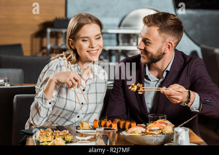 Attractive smiling couple eating together sushi rolls in restaurant - Stock Photo