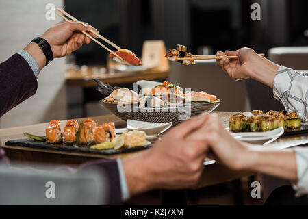 Partial view of couple holding hands while eating together sushi rolls in restaurant - Stock Photo