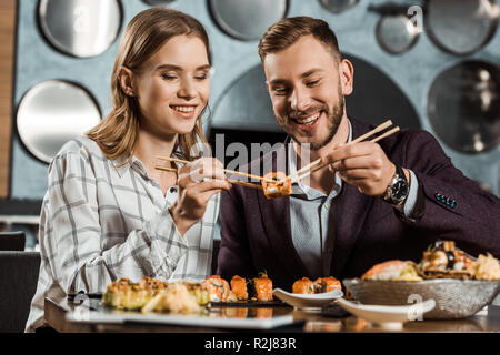 Smiling attractive young adult couple eating sushi together in restaurant - Stock Photo
