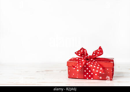 Red Christmas gift box with big red bow on white background. Copy space - Stock Photo