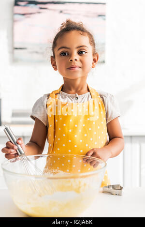 adorable african american kid preparing and whisking dough in kitchen - Stock Photo